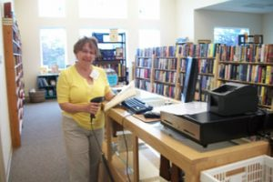 woman standing at used book store checkout